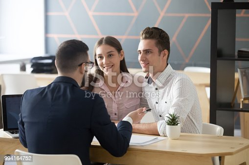 istock Insurance agent consulting millennial couple in office 994164752