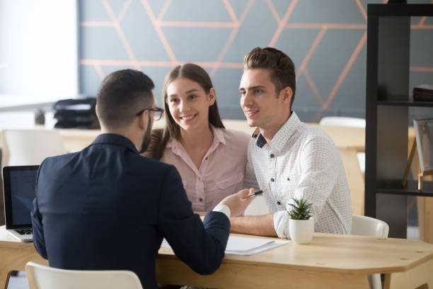 insurance agent consulting millennial couple in office - bankers stock photos and pictures