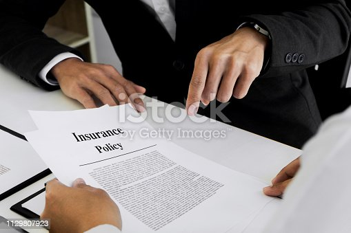istock Insurance agent explain consulting with customer to signing the policy form. 1129807923