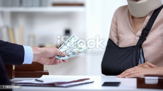 istock Insurance agent giving dollar payment to woman with broken hand, life assurance 1183325391