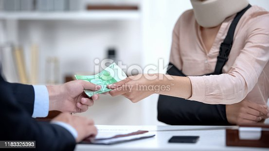 istock Insurance agent giving euro money to injured woman, payment for treatment 1183325393