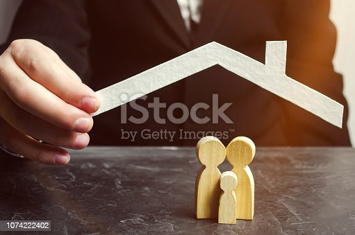958039576 istock photo Insurance agent holds a house over the family. The concept of insurance of family life and property. Family care and helping hand. Health insurance. Health care. Security and Property Protection 1074222402