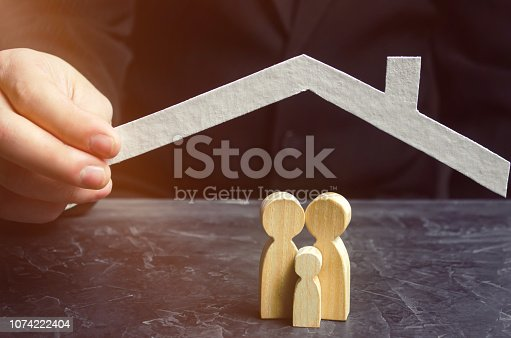 958039576 istock photo Insurance agent holds a house over the family. The concept of insurance of family life and property. Family care and helping hand. Health insurance. Health care. Security and Property Protection 1074222404