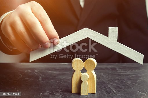 958039576 istock photo Insurance agent holds a house over the family. The concept of insurance of family life and property. Family care and helping hand. Health insurance. Health care. Security and Property Protection 1074222406
