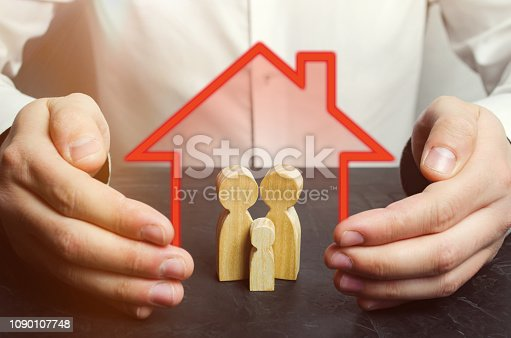 958039576 istock photo Insurance agent holds hands over family. Family care and helping hand concept. Health insurance. Health care. Security and Property Protection. The concept of insurance of family life and property. 1090107748