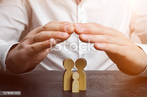 958039576 istock photo Insurance agent holds hands over family. The concept of insurance of family life and property. Family care and helping hand concept. Health insurance. Health care. Security and Property Protection 1078091020