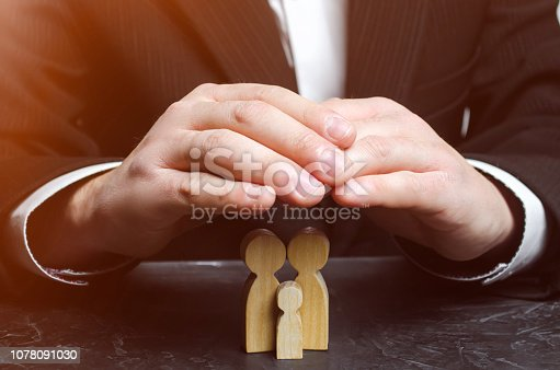 958039576 istock photo Insurance agent holds hands over family. The concept of insurance of family life and property. Family care and helping hand concept. Health insurance. Health care. Security and Property Protection 1078091030