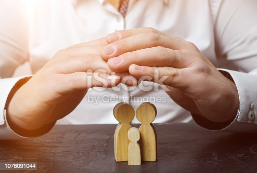 958039576 istock photo Insurance agent holds hands over family. The concept of insurance of family life and property. Family care and helping hand concept. Health insurance. Health care. Security and Property Protection 1078091044