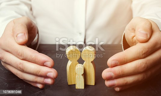 958039576 istock photo Insurance agent holds hands over family. The concept of insurance of family life and property. Family care and helping hand concept. Health insurance. Health care. Security and Property Protection 1078091046