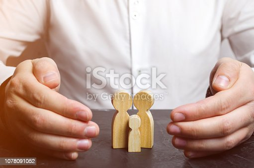 958039576 istock photo Insurance agent holds hands over family. The concept of insurance of family life and property. Family care and helping hand concept. Health insurance. Health care. Security and Property Protection 1078091052