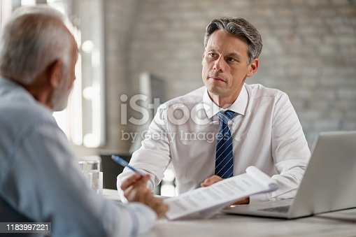 1072035844istockphoto Insurance agent offering a contract to senior customer in the office. 1183997221