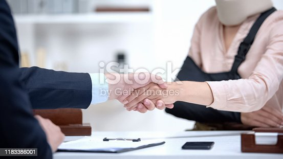 istock Insurance agent shaking hand with woman in arm sling, psychological support 1183386001