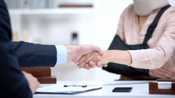 Insurance agent shaking hand with woman in arm sling, psychological support stock photo