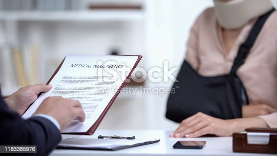 istock Insurance agent signing Medical negligence to accident victim with broken hand 1183385976
