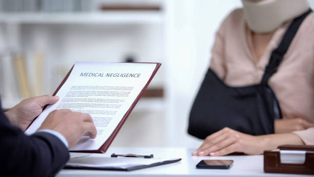 Insurance agent signing Medical negligence to accident victim with broken hand stock photo