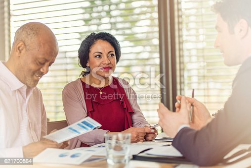 istock Insurance agent talking to older couple of african ethnicity 621700864