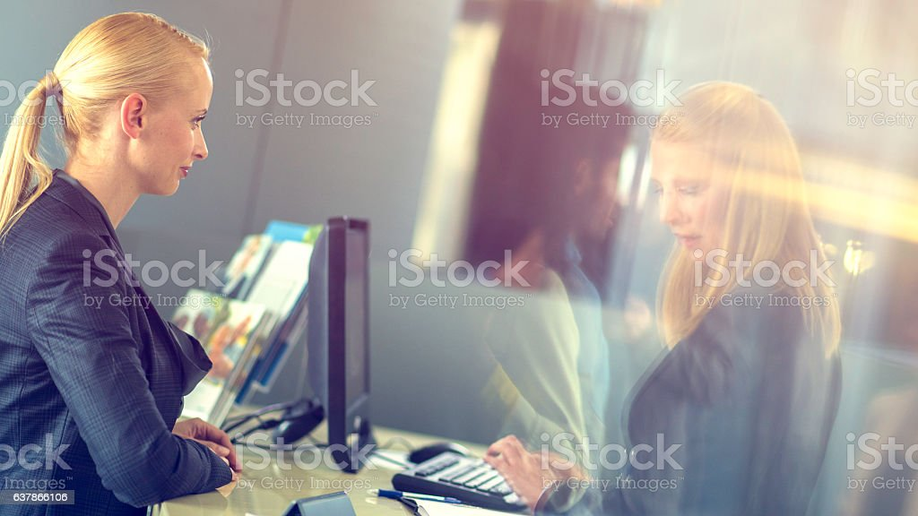 Insurance agent typing a woman's info into the computer - Photo