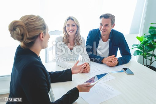 Insurance agent with couple looking through documents. The agent is holding a digital tablet. Couple are casually dressed. They sitting at a table at home and are looking a little happy and smiling.
