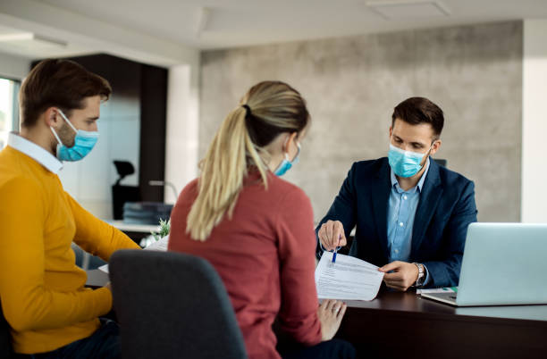 Insurance agent with face mask explaining terms of a contract to a couple during the meeting. stock photo