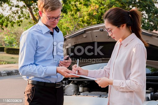 istock Insurance agent writing document on clipboard examining car after accident, Insurance concept 1150200829