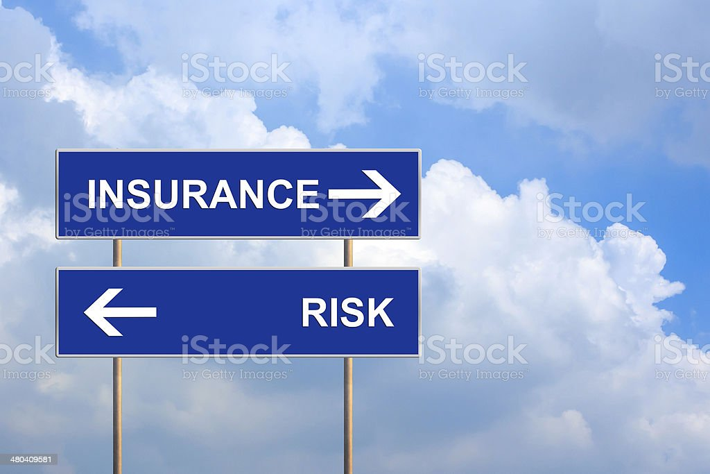 Insurance and risk on blue road sign stock photo