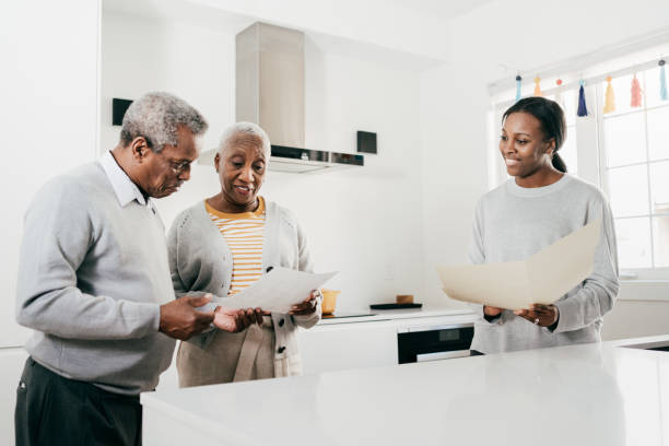 Insurance broker and senior couple at home with folders stock photo