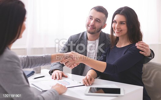 994164754 istock photo Insurance broker handshaking with young couple of clients 1201191901