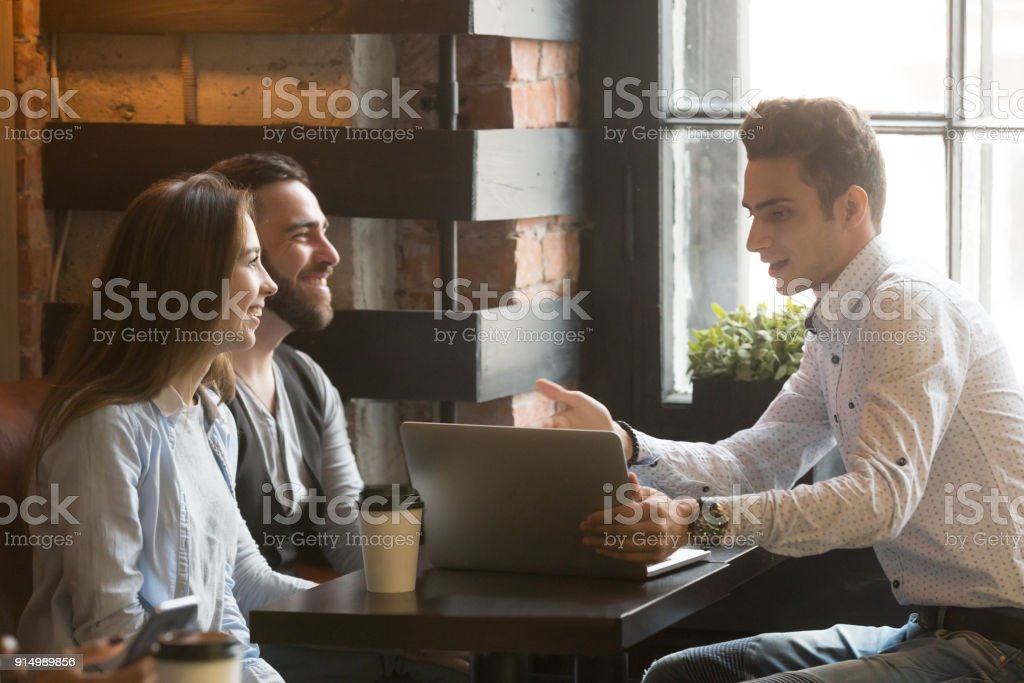 Insurance broker or salesman making offer to couple in cafe stock photo