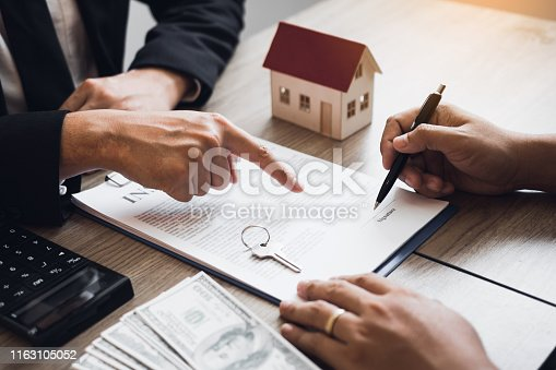 481337750istockphoto Insurance brokers are pointing to insurance contract signing and are explaining to customers at the office. 1163105052