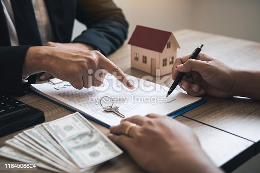481337750istockphoto Insurance brokers are pointing to insurance contract signing and are explaining to customers at the office. 1164508624