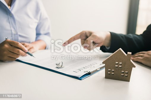 481337750istockphoto Insurance brokers are pointing to insurance contract signing and are explaining to customers at the office. 1176463972