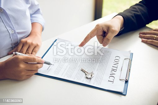 481337750istockphoto Insurance brokers are pointing to insurance contract signing and are explaining to customers at the office. 1182360093