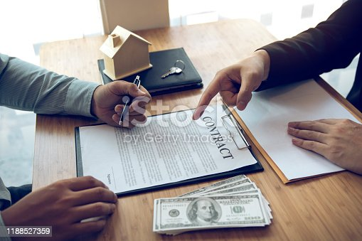 481337750 istock photo Insurance brokers are pointing to insurance contract signing and are explaining to customers at the office. 1188527359