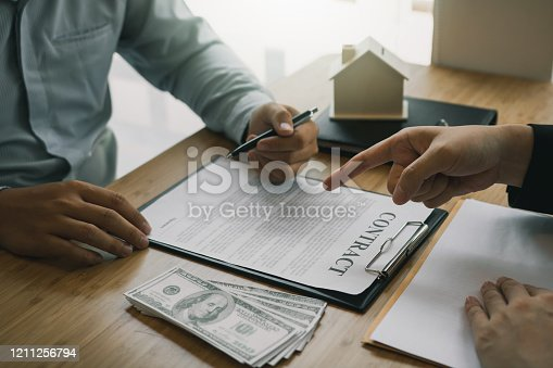 481337750 istock photo Insurance brokers are pointing to insurance contract signing and are explaining to customers at the office. 1211256794