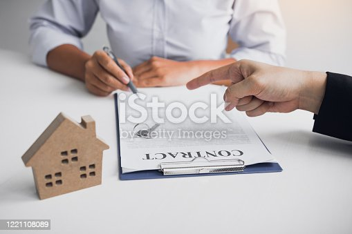 481337750 istock photo Insurance brokers are pointing to insurance contract signing and are explaining to customers at the office. 1221108089