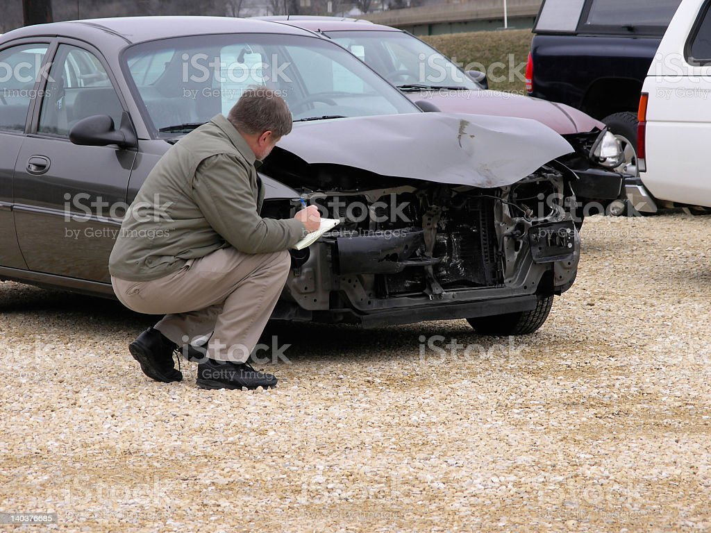Insurance claim adjuster inspects front of vehicle royalty-free stock photo