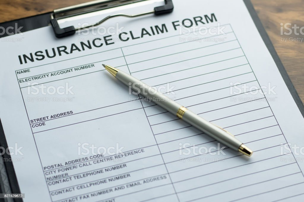 Insurance claim form with pen on  wooden table. selective focus stock photo