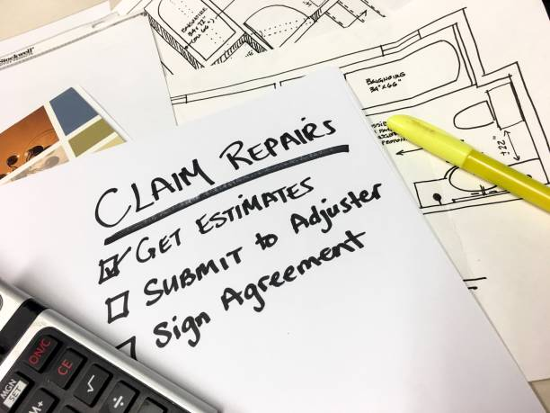 Insurance Claim Repairs and Payment Checklist Blueprints Calculator on Desk stock photo
