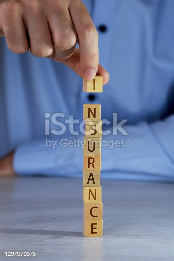 Insurance concepts. Hand arranging wood blocks and word of insurance written on the wood blocks