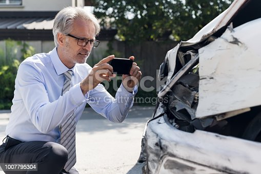 Insurance expert examining crushed car after accident