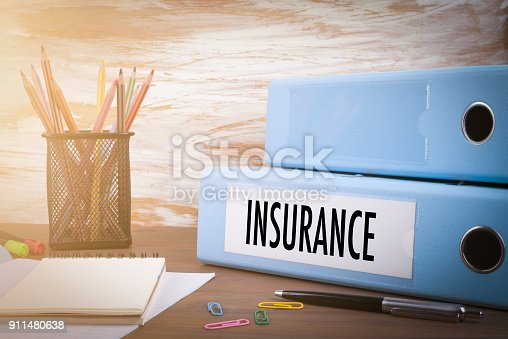 863128060 istock photo insurance, Office Binder on Wooden Desk. On the table colored pencils, pen, notebook paper 911480638