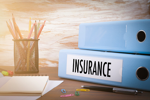 istock insurance, Office Binder on Wooden Desk. On the table colored pencils, pen, notebook paper 911480638