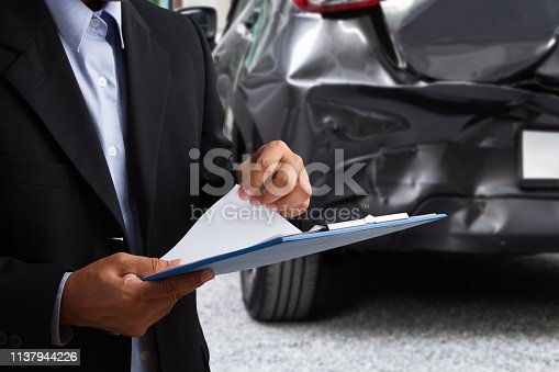 istock insurance officer writing on clipboard while insurance agent examining black car after accident. 1137944226