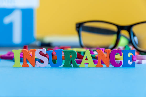 Insurance - word composed of small colored letters on business workplace of broker. Illustration of the concept of insurance stock photo