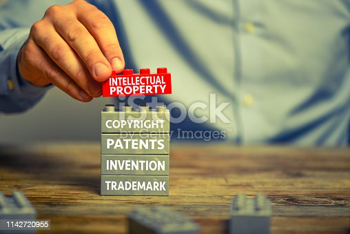 Businessman staking lego blocks. He is adding a red block showing the words 'Intellectual property' on top of grey blocks with related words