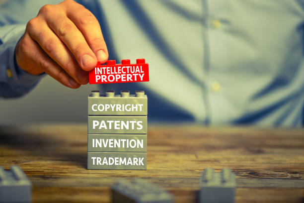 Intellectual property Businessman staking plastic block blocks. He is adding a red block showing the words 'Intellectual property' on top of grey blocks with related words intellectual property stock pictures, royalty-free photos & images