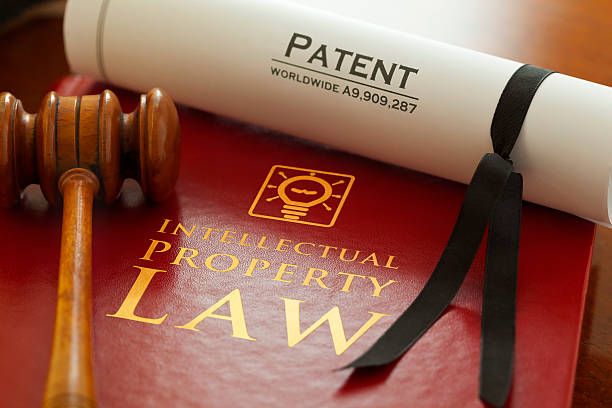 Intellectual Property Inspector. Graphic logo is my artwork. Patent Number is fictitious. Thanks.     Red leather Intellectual Property Law book with with gold embossed type and iconic light bulb, ideas icon logo, with a judges gavel and a generic A4 Patent document. intellectual property stock pictures, royalty-free photos & images