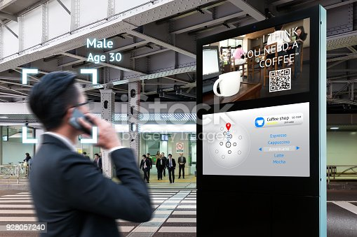 istock Intelligent Digital Signage , Augmented reality marketing and face recognition concept. Interactive artificial intelligence digital advertisement navigator direction for retail coffee shop. 928057240