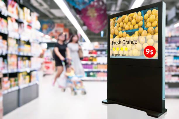 Inteligente Digital Signage, marketing de realidad aumentada y concepto de reconocimiento de rostro. Inteligencia artificial interactivo digital anuncio fresco naranja granja orgánica en centro comercial de venta por menor. - foto de stock
