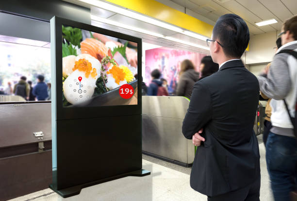 Intelligent Digital Signage , Augmented reality marketing and face recognition concept. Interactive artificial intelligence digital advertisement sushi Japanese restaurant in subway or sky train. stock photo